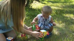 La mamma gioca con suo figlio, sguardi bei di un neonato, giochi un giocattolo, pelle leggera, occhi azzurri, capelli biondi, con stock footage