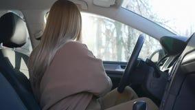 La mamma in grande aspettativa chiude la porta di automobile e mette sopra la cintura di sicurezza che si siede nel veicolo in la archivi video