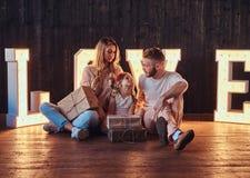 La mamma, il papà e la figlia si siede insieme ai regali nella sala decorata con le lettere voluminose con l'illuminazione fotografia stock