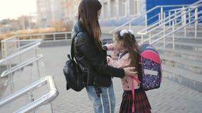 La mamma incontra una piccola figlia un primo selezionatore vicino all'edificio scolastico stock footage