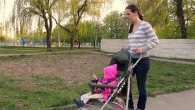La mamma indossa una neonata che si siede in un passeggiatore Camminando lungo il percorso video d archivio