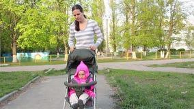La mamma indossa una neonata che si siede in un passeggiatore Camminando lungo il percorso archivi video