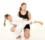 La mamma insegna al karatè di respinta della perforazione della figlia Immagine Stock Libera da Diritti