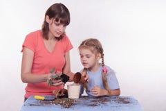 La mamma insegna alla figlia a trapiantare la stanza del fiore immagine stock libera da diritti
