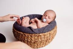 La mamma mette il bambino nel canestro Immagine Stock