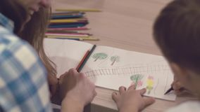La mamma preoccupantesi aiuta il suo piccolo figlio affascinante a disegnare stock footage