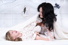 La mamma solletica la figlia Immagine Stock