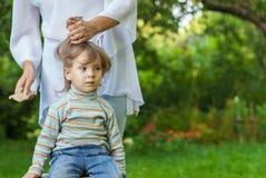 La mamma stava pettinando i capelli con la figlia Fotografia Stock