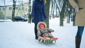 La mamma tira il suo poco bambino su una slitta nell'inverno stock footage