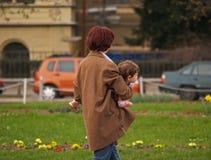 La mamma trasporta un bambino in mani Immagini Stock Libere da Diritti