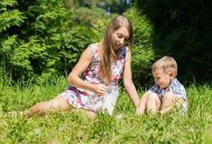 La mamma versa il piccolo latte del figlio dalla brocca sulla radura della foresta Fotografia Stock Libera da Diritti