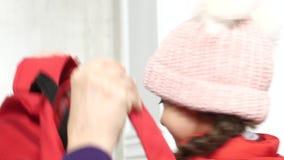 La mamma veste uno zaino a sua figlia che va a scuola stock footage