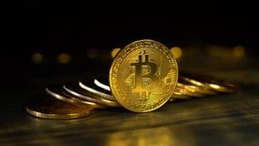 La manciata di bitcoins impilati sopra a vicenda su una tabella una sta su un bordo di un bokeh nero del fondo dell'oro video d archivio