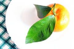 La mandarine avec le vert part sur le plat blanc, vue supérieure Photos libres de droits