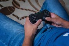 La manette de la console est en gros plan dans les mains d'un homme Équipez jouer sur la manette dans une console de jeu Photo libre de droits