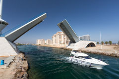 La Manga - SPAIN, AUGUST 25 2014: Drawbridge over water channel and Pleasure boat Stock Photos