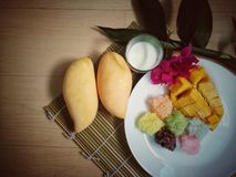 la mangue douce avec du riz collant coloré et le lait de noix de coco bourdonnent Photo stock