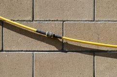 La manguera de jardín con el acoplamiento de la reparación cuelga en una pared de bloques de piedra lisos Fondo, serie de la text foto de archivo libre de regalías