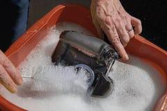 La manière fausse de nettoyer un appareil-photo photographie stock libre de droits