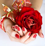 La manicura roja con la cinta de oro y se levantó imagen de archivo