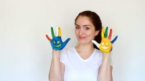 La manifestazione sorridente della ragazza della ragazza dello studente del ritratto ha dipinto le mani variopinte con i sorrisi  video d archivio