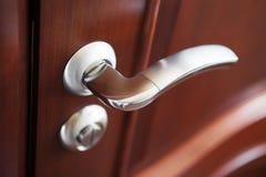 La maniglia di porta del metallo su una porta marrone Fotografie Stock