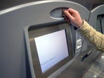 La mano añade euro en una máquina expendedora fotos de archivo
