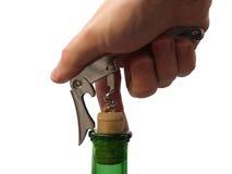 La mano abre la botella con el sacacorchos fotos de archivo