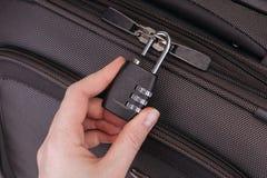 La mano abre la cerradura de combinación de la maleta fotos de archivo libres de regalías