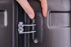La mano abre la cerradura de combinación de la maleta fotos de archivo
