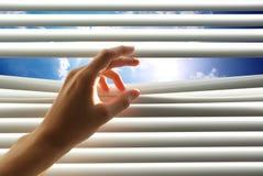 La mano abre la persiana fotos de archivo