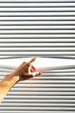 La mano abre la persiana imagen de archivo libre de regalías