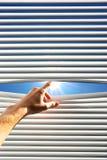La mano abre la persiana imagenes de archivo