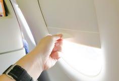 La mano abre la ventana del aeroplano Imagen de archivo libre de regalías