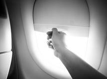 La mano abre la ventana del aeroplano Fotos de archivo