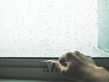 La mano abre la ventana para considerar la lluvia fotografía de archivo