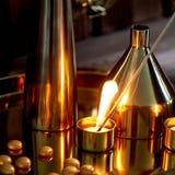La mano accende una candela con una partita lunga con una fiamma luminosa La gamma dorata calda Anche comodit? Molti vasi di fotografie stock libere da diritti