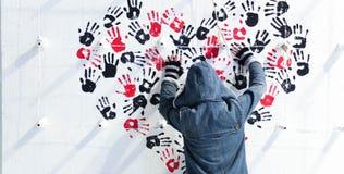 La mano acquerella nera e rossa della mano tesa della ragazza, modella sulla parete Fotografie Stock