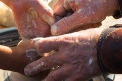 La mano adulta ha alimentato le mani del ` s del bambino a lavoro con una ruota del ` s del vasaio fotografia stock libera da diritti