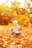 La mano adulta sostiene las hojas amarillas del otoño del bebé en la sentada del niño de la puesta del sol, Imagen de archivo libre de regalías