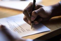 La mano africana maschio scrive la firma sul documento corporativo legale della carta immagine stock