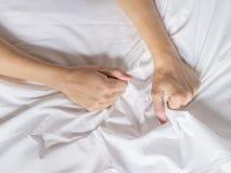 La mano agarra compresiones una hoja de cama arrugada blanco en una habitación, una muestra del éxtasis, sensación del placer u o imágenes de archivo libres de regalías