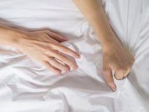 La mano agarra compresiones una hoja de cama arrugada blanco en una habitación, una muestra del éxtasis, sensación del placer u o fotos de archivo libres de regalías