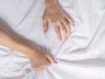 La mano agarra compresiones una hoja de cama arrugada blanco en una habitación, una muestra del éxtasis, sensación del placer u o imagen de archivo