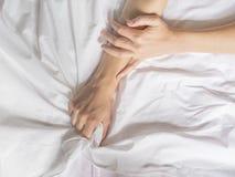 La mano agarra compresiones una hoja de cama arrugada blanco en una habitación, una muestra del éxtasis, sensación del placer u o imagen de archivo libre de regalías
