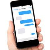 La mano aislada de la mujer que sostiene el teléfono con SMS charla en una pantalla Foto de archivo libre de regalías