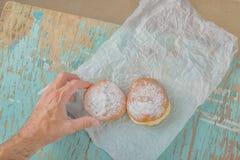 La mano alcanza para el buñuelo azucarado dulce en la tabla rústica Imágenes de archivo libres de regalías