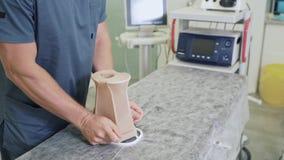 La mano alta vicina di medico prepara le calze di compressione prima di chirurgia archivi video