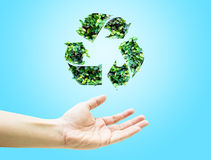 La mano aperta con la foglia verde ricicla l'icona su fondo blu-chiaro Immagine Stock