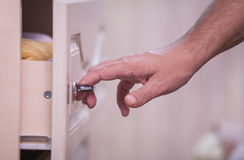 La mano apre un armadietto Fotografia Stock Libera da Diritti